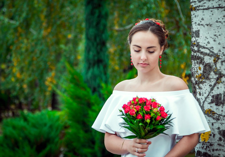 frilly: Portrait of beautiful young bride in white frilly dress with open shoulders and red earrings looking at wedding bouquet of small red roses in her hand, standing in the autumn park