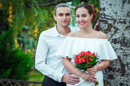 Happy loving wedding couple in the autumn park. Young handsome groom embracing his beautiful smiling bride in white dress, holding bouquet of red roses Stock Photo