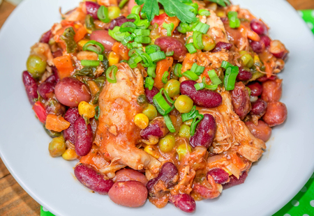 Closeup of homemade stewed beans with chicken meat green peas and vegetables served with cut green onion and parsley on a white plate on a wooden table Stock Photo