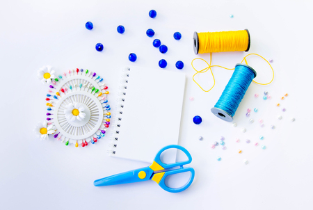 Sewing spools of blue and yellow caprone threads, blank spiral notepad, plastic scissors, glass beds and colorful pins on white background Stock Photo