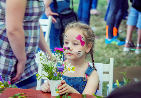 Zaporizhia  Ukraine- May 28, 2017: Charity Family festival: Small girl with kitten mask face paint party at outdoors florist workshop, admiring self made beautiful flowers arrangement. Art and craft children activity.