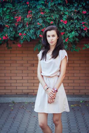 Portrait der schönen jungen Brünette Frau, trägt kurze lässig Kleid, stand vor einer Mauer von blühenden Trompete Creeper Pflanze bedeckt. Straßenmode. Standard-Bild - 82938944