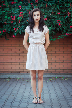 Full length portrait of beautiful young brunette woman, wearing short casual dress, standing in front of a brick wall covered by blooming trumpet creeper plant. Street fashion. 版權商用圖片