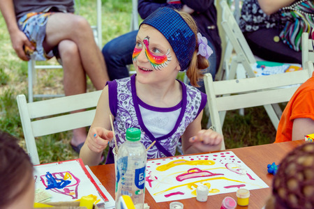 Zaporizhia  Ukraine- May 28, 2017: Charity Family Festival: smiling girl with painted face mask, participating at art and craft outdoors workshop, making colorful drawings with gouache Editorial