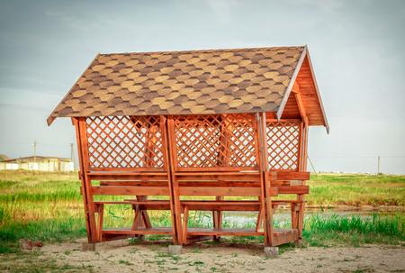 New wooden gazebo on a pond sandy coast Stock Photo