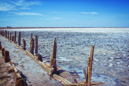 Dry in summer pink salty lake with path, hedged by weathered old wooden sticks. Mud, salt and brine puddles, used in spa procedures and therapy. Sivash lake.