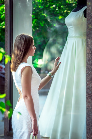 show window: Elegant young woman admiring beautiful white wedding dress at the window of bridal boutique. Dreaming about wedding concept. Stock Photo