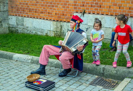 Krakow  Poland - August 14, 2017: Wawel Royal Castle, street musician - man, wearing traditional Polish clothes, playing accordion, entertaining children Editorial
