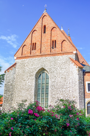 restored: View of the old stone Catholic church building with orange brick roof, arcade window and blooming tea rose bush on a sunny summer day, Poland, Krakow Stock Photo