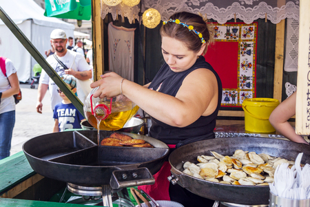 Krakow  Poland - August 15, 2017: main Market Square - Polish traditional food outdoors open kitchen - young woman pouring oil into frying pan.