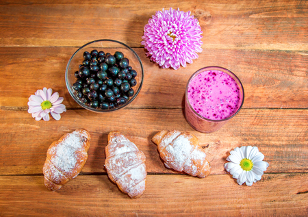 Berry smoothie in a glass, black currant, croissants with a sugar powder, pink and white aster flowers on a wooden background Standard-Bild