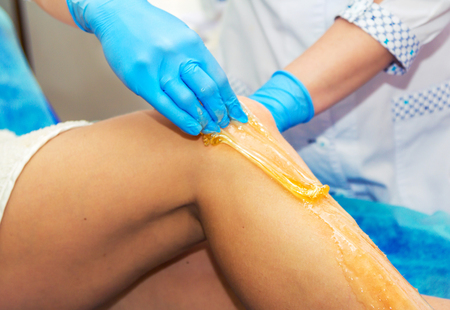 Close-up hands of cosmetologist in blue gloves applying paste for sugaring depilation, hair removal beauty procedure.