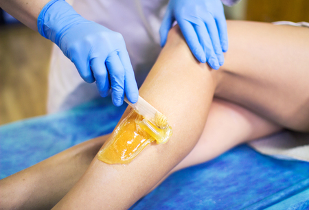 Close-up hands of cosmetologist in blue gloves applying paste for sugaring depilation on leg with wooden spatula, hair removal beauty procedure. Stock Photo