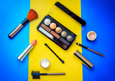 Cosmetic beauty products for make-up on bright colorful background - eye shadows, brushes, lipstick, face cream and highlighter base in small jars. Stock Photo