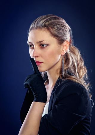 Portrait of beautiful woman in black gloves holding finger near lips in silence. Secret concept.
