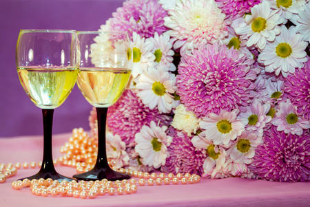 Two elegant glasses of white wine or champagne with beautiful stock photo two elegant glasses of white wine or champagne with beautiful aster and chrysanthemum flowers bouquet and pearl beads on background mightylinksfo