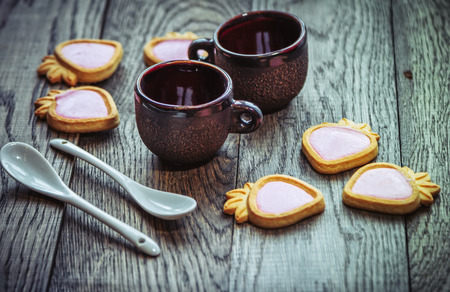 Ceramic coffee cups, strawberry shape cookies with pink cream and white spoons on a wooden table. Sweet snack or breakfast.