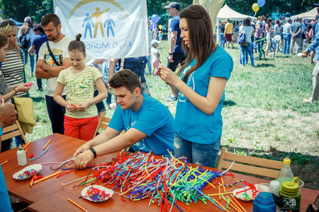 Zaporizhia / Ukraine- June 2, 2018: volunteers - young man and woman - preparing for arts and craft workshop for children on city family charity festival