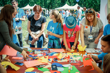 Zaporizhia / Ukraine- June 2, 2018: children and their parents participating in making colorful paper flowers workshop on city family charity festival Redakční