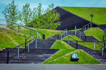 Katowice / Polska - 2 maja 2018: widok na zielone trawniki i symetryczne czarne schody w pobliżu budynku International Congress Hall w centrum miasta z nowoczesnym designem