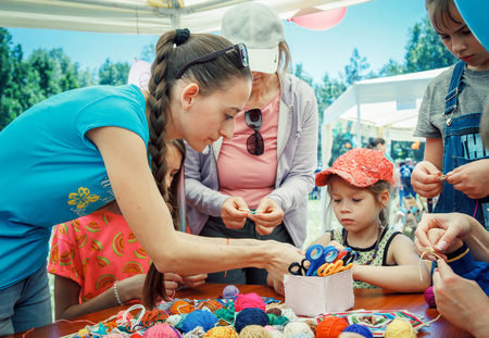 Zaporozhia  Ukraine- June 2, 2018: Charity Family festival-young woman - volunteer explaining to small girl how to knit