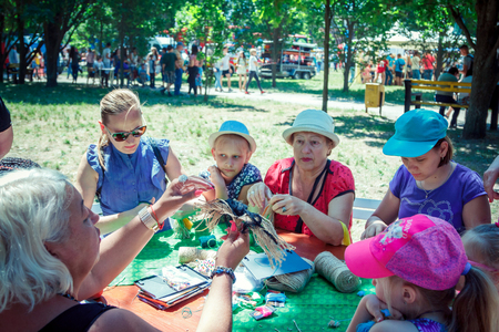 Zaporizhia  Ukraine- June 2, 2018: young woman - journalist interviewing teen girls, participating in making colorful paper flowers workshop on city family charity festival in a city park.