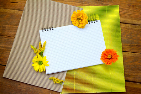 Blank spiral notepad with yellow and orange flowers and corrugated cardboard paper on the table.