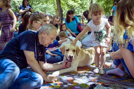 Zaporizhia  Ukraine- June 2, 2018: Children and their specially trained labrador at the city park