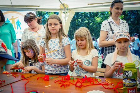 Zaporozhia / Ukraine- June 2, 2018: Charity Family festival - small girls participating at art and craft outdoor workshop, playing with colorful chenille sticks, making toys and bracelets. children activity and entertainment.