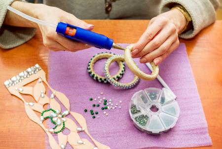 Manos de mujer de primer plano, decorando pulseras con pedrería brillante de colores, pegando cristales sobre una base textil con pistola de pegamento caliente. Concepto de proceso artesanal.