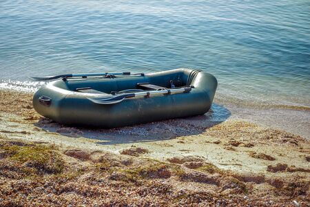 Tranquil landscape with calm sea water, sandy shore and inflatable rubber fisher boat, sunny summer day.