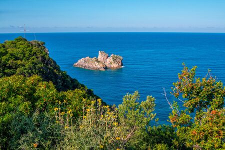 Beautiful landscape with sea, mountain and cliffs in a blue water, green trees, flowers and blooming bushes. Corfu Island, Greece.