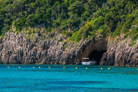 Seascape - lagoon with turquoise water, mountain with cliffs, green trees, blooming bushes, rocks in a blue water, and cruise touristic boat in cave. Corfu Island, Greece. Imagens