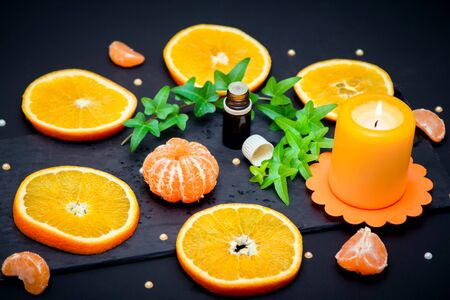 Citrus aroma oil concept – close up glass bottle with essence, ripe juicy orange and tangerine slices, candle and ivy branch with green leaves on black background.
