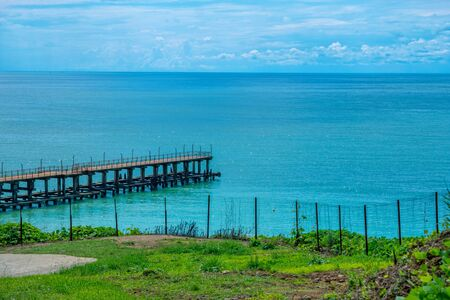 Summer landscape with calm sea, wooden pier, green grass on the coast and blue sky