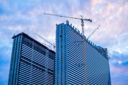 High rise buildings construction site with crane over colorful - blue, pink and purple sunset sky with clouds. Modern architecture. 写真素材