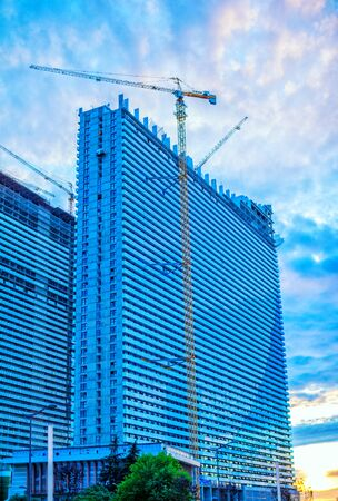 High rise building construction process with crane. Modern architecture.