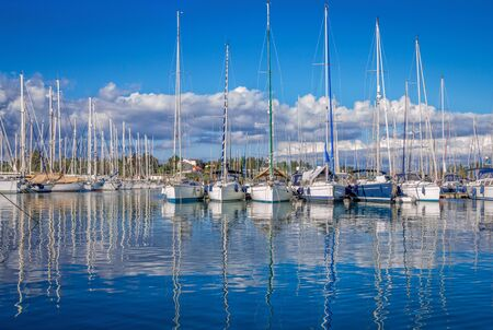 View of port marina - white yachts and blue sky with white clouds reflecting on a calm water surface. Beautiful summer landscape. Stock Photo