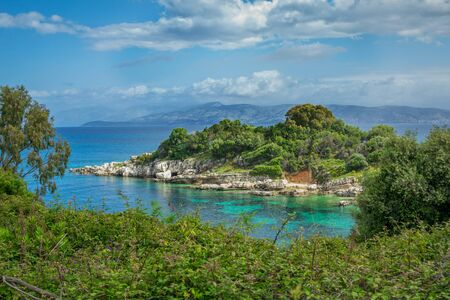 Beautiful summer landscape of sea lagoon with turquoise calm water, cliffs and rocks on the shore, meadow with green grass, trees and bushes, mountains on the horizon. Corfu Island, Greece Stock Photo