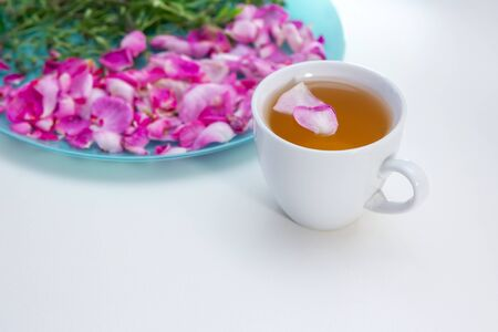 Homemade herbal tea in a white cup. Tea rose petals and thyme - ingredients for hot healthy drink