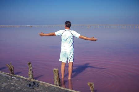 Brunet man relaxing on pink salty Sivash Lake near Azov Sea, colored by microalgae Dunaliella salina, enriching water of the lake by beta-carotene