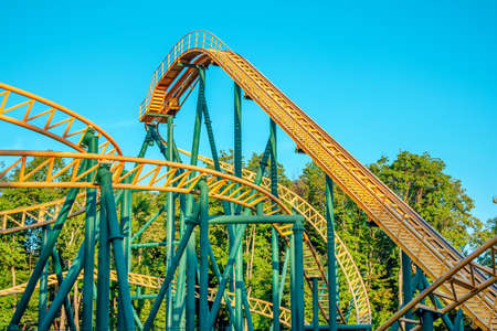 Part view of roller coaster track with blue sky on background at amusement park