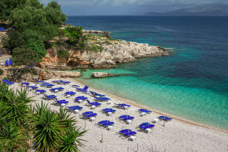 View of empty beach - blue deck chairs and umbrellas near sea water, cliffs and rocks, green trees and bushes, mountains on the horizon. Landscape of abandoned summer resort.