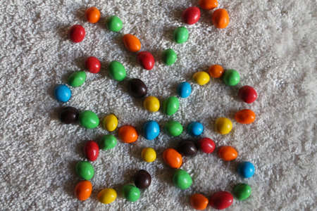 gaily: butterfly from sweet chocolate candy s drops different colours Stock Photo