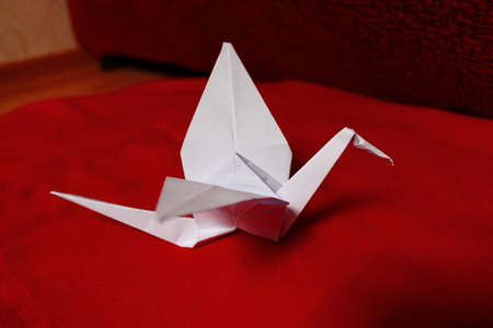 crane origami: white paper crane origami making on the red