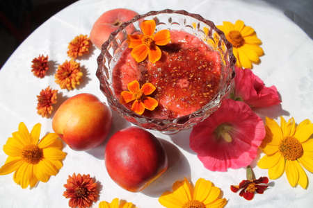 crystal bowl: fresh raspberry jam in crystal bowl decorated orange bloom flowers and two ripe peaches