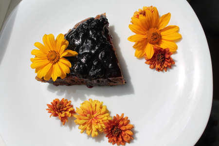 dulcet: appetizing vegetarian chocolate  piece of cake decorated with orange  flowers
