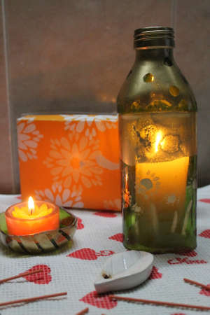 beautify: glass fragile lantern from bottle decoreted flowers and burning candle inside Stock Photo