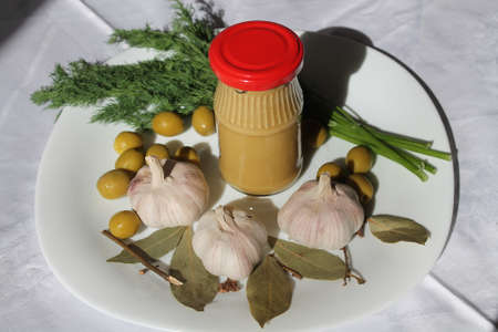 piquant: heads of pink garlic, olive,tuft of green drill, box of mustard, laurel leaves ingredient for piquant sauce