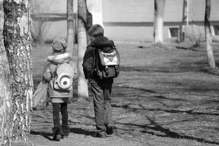 rapprochement: two young girl and boy walk together on spring street in sunny day